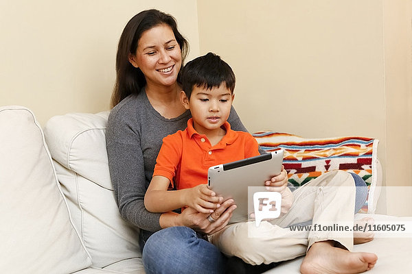 Son sitting in lap of mother using digital tablet