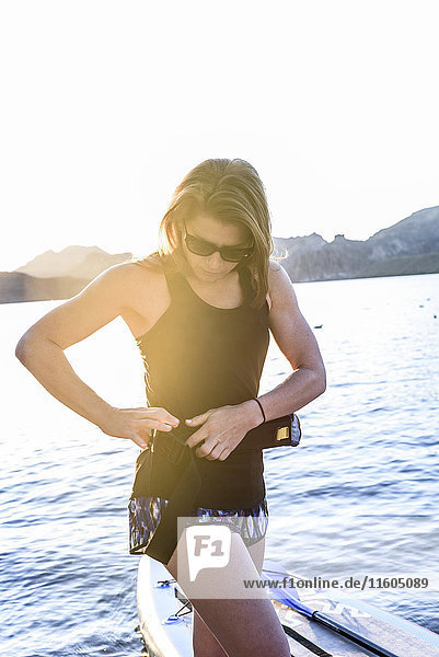 Caucasian woman fastening belt near paddleboard