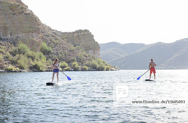 Caucasian couple on paddleboards in river