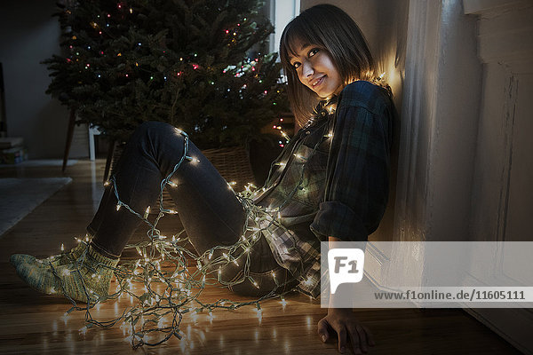 Mixed Race woman sitting on floor wrapped in string lights near Christmas tree