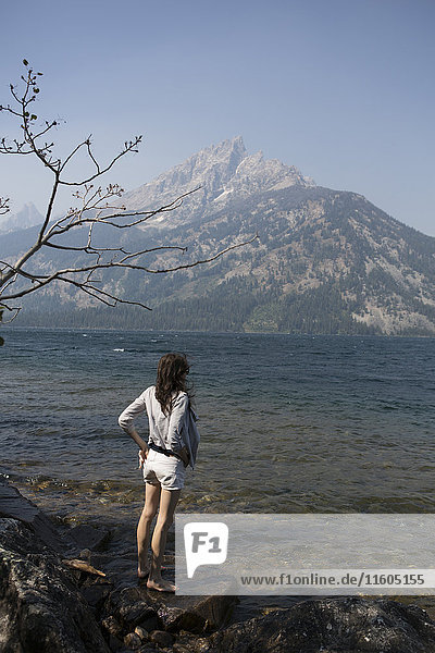 Caucasian woman standing in Jenny Lake admiring Great Teton mountains  Wyoming  United States