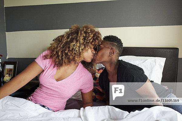 Black women kissing in bed