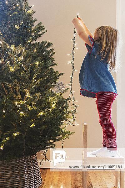 Caucasian girl hanging lights on Christmas tree