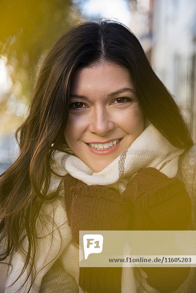Smiling Caucasian woman wearing gloves and scarf