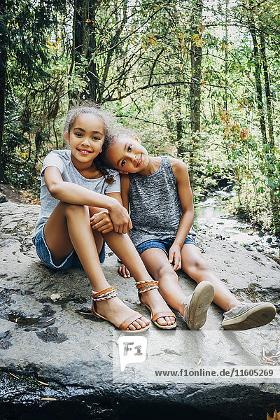 Portrait of smiling Mixed Race girls sitting on rock