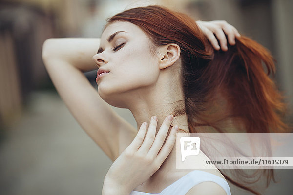 Caucasian woman holding hair and rubbing neck