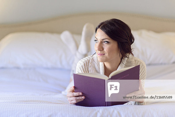 Pensive Caucasian woman laying on bed reading book