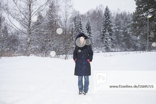 Ganzkörperporträt einer erwachsenen Frau  die auf einem schneebedeckten Feld steht.