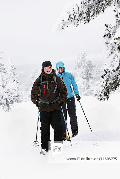 Couple cross country skiing in winter forest