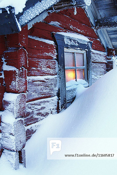 Snow covering red hut