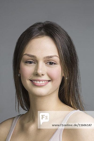 Nahaufnahme einer schönen jungen Frau  die vor grauem Hintergrund lächelt.
