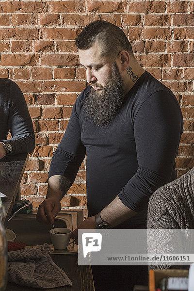 Männlicher Friseur beim Mischen von Kaffee inmitten von Mitarbeitern an der Ziegelwand im Friseursalon