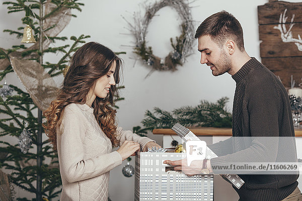 Seitenansicht des lächelnden Paares beim Verpacken von Weihnachtsgeschenken zu Hause