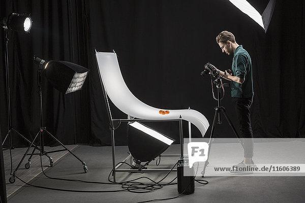 Seitenansicht des selbstbewussten Fotografen beim Fotografieren von Lebensmitteln im Studio