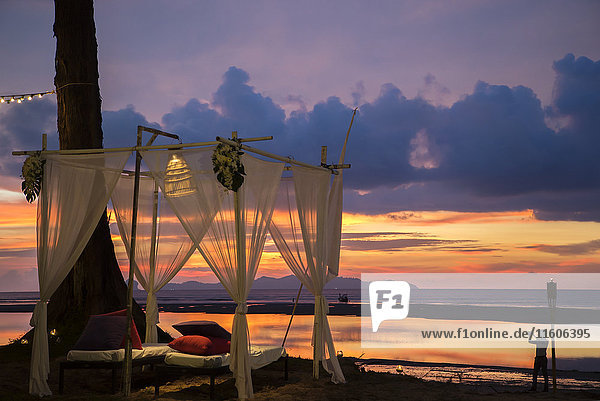 Outdoor bed on beach at sunset