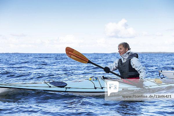 Woman kayaking on sea