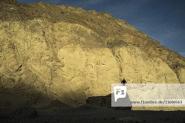 Silhouette eines Mannes  der auf dem Felsen gegen den Berg steht  Death Valley  Nevada  USA Silhouette eines Mannes, der auf dem Felsen gegen den Berg steht, Death Valley, Nevada, USA