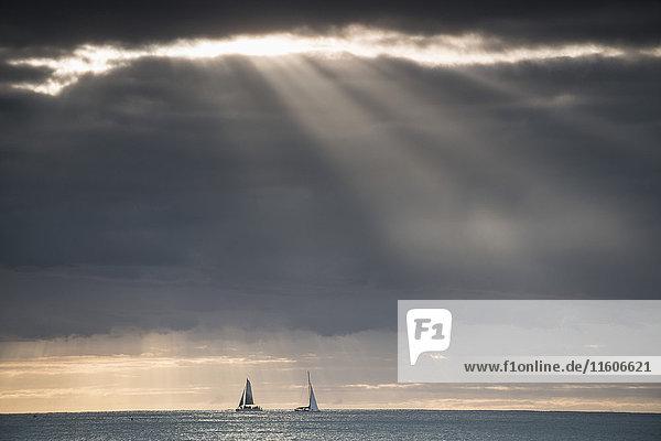 Fernsicht auf Yachten im Meer gegen den dramatischen Himmel Fernsicht auf Yachten im Meer gegen den dramatischen Himmel