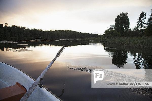 Abgeschnittenes Bild eines Ruderbootes  das bei Sonnenuntergang auf dem See festgemacht hat