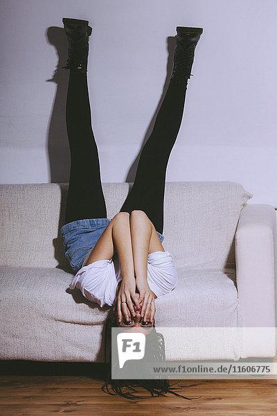 Frau auf Sofa liegend mit Füßen an der weißen Wand