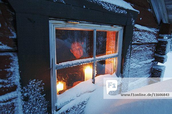 Man looking through window of log cabin