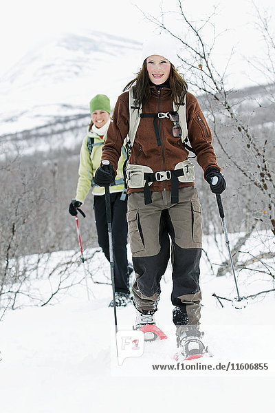 Smiling women snowshoeing