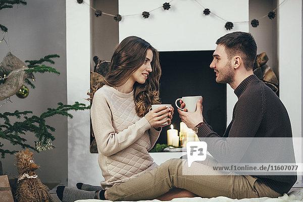 Lächelndes Paar beim Kaffeetrinken auf dem Teppich zu Hause zu Weihnachten