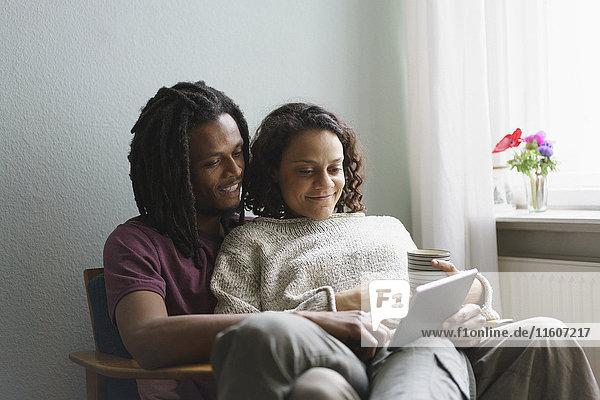 Junges multiethnisches Paar  das zu Hause auf einem Sessel sitzt und ein digitales Tablett benutzt.