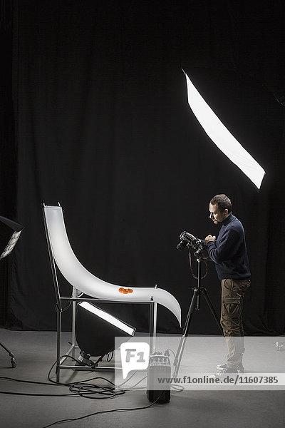 Volle Länge des Fotografen  der Essen im Studio vor schwarzem Hintergrund fotografiert.