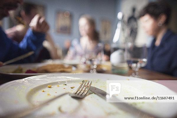 Nahaufnahme der Gabel auf dem Teller mit Leuten  die im Hintergrund am Esstisch sitzen.