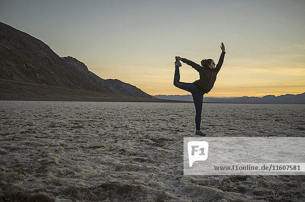 Volle Länge der jungen Frau beim Yoga in der Wüste bei Sonnenuntergang  Death Valley  Nevada  USA Volle Länge der jungen Frau beim Yoga in der Wüste bei Sonnenuntergang, Death Valley, Nevada, USA