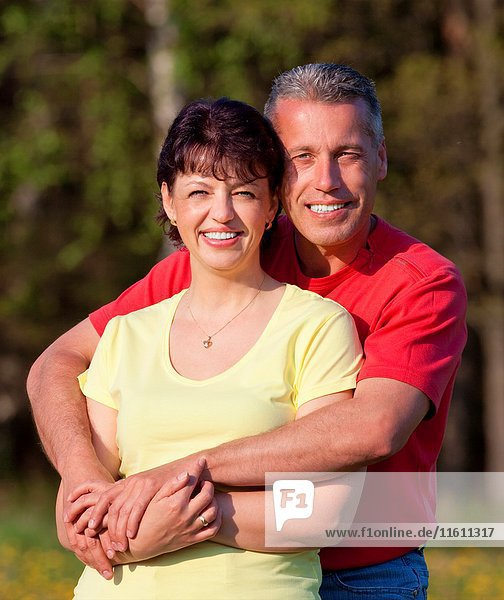 Portrait of husband and wife standing outdoors holding each other.