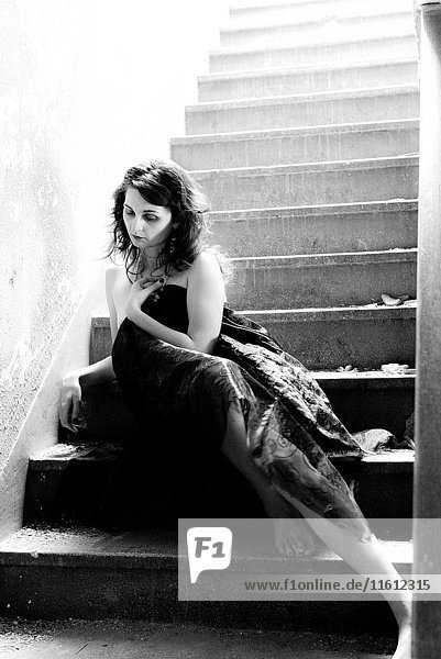 A partially nude 25 year old woman wrapped in fabric sitting alone on a stairway in an old building  black and white.