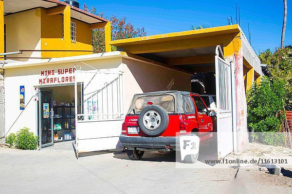 Mini tiny supermarket called' mini Miraflores' set under a yellow house in the middle of nowhere outside of Cabo San Lucas. The red small SUV is park under the garage. Blue sky  sunny day in Cabo San Lucas  Baja California  Mexico