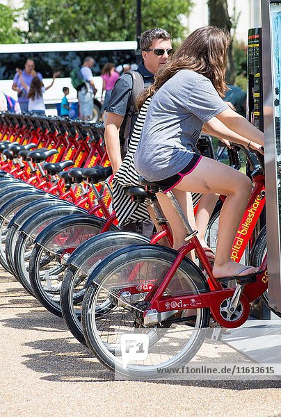 Bike to share in the capital of the USA. Red Bicycles for rent for tourist in a big cosmopolitan city. A caucasian man in his 30's 40's 50's discuss the possibly of renting a bike with his teenage daughter trying the bike.