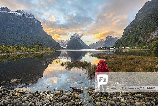 Touristin schaut in die Landschaft  Mitre Peak spiegelt sich im Wasser  Sonnenuntergang  Milford Sound  Fiordland Nationalpark  Te Anau  Southland  Südinsel  Neuseeland  Ozeanien