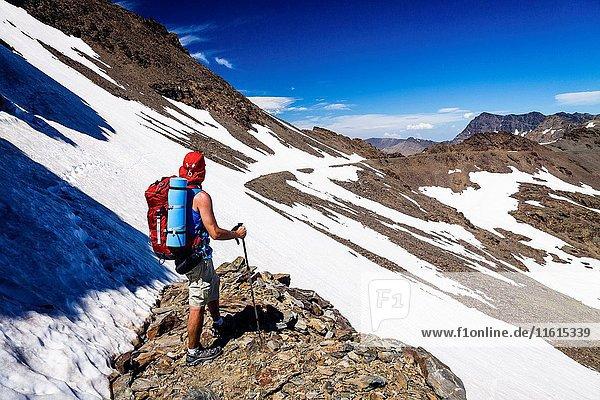 Trekker facing the Tajo de los Machos on his way to Mount Mulhacen  the highest peak in the Iberian Peninsula. Sierra Nevada  Granada  Spain.