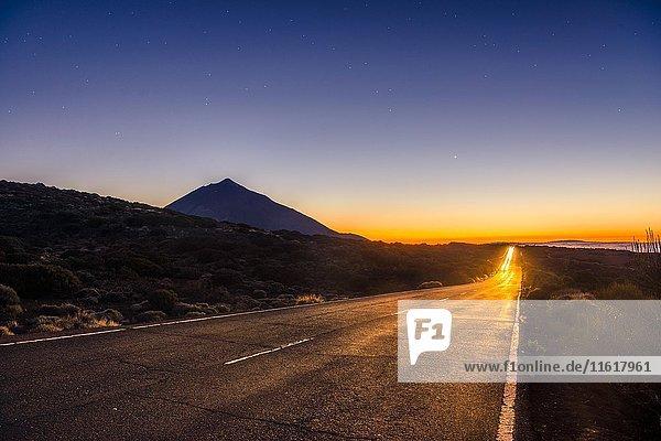 Lichtspuren vom Auto auf Bergstraße  Landstraße  Sonnenuntergang  Vulkan Teide im Gegenlicht  Silhouette  Vulkanlandschaft  Sternenhimmel  Nationalpark El Teide  Teneriffa  Kanarische Inseln  Spanien  Europa