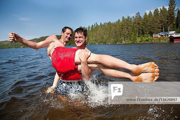 Brothers play fighting in the water  countryside of northern Sweden.