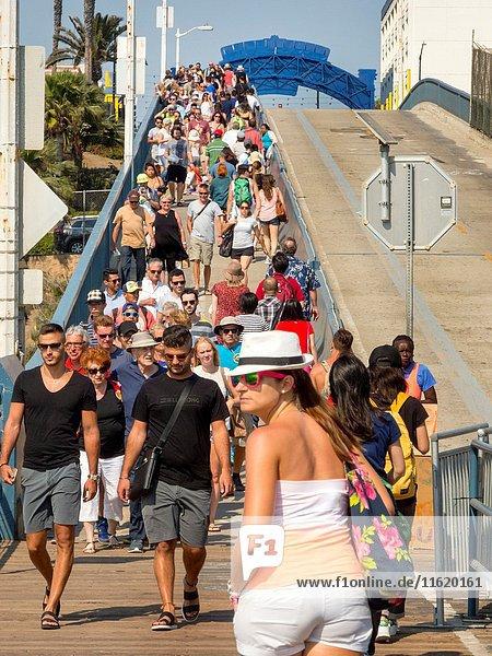 A multiracial holiday crowd throngs a bridge to the amusement pier in Santa Monica  CA.