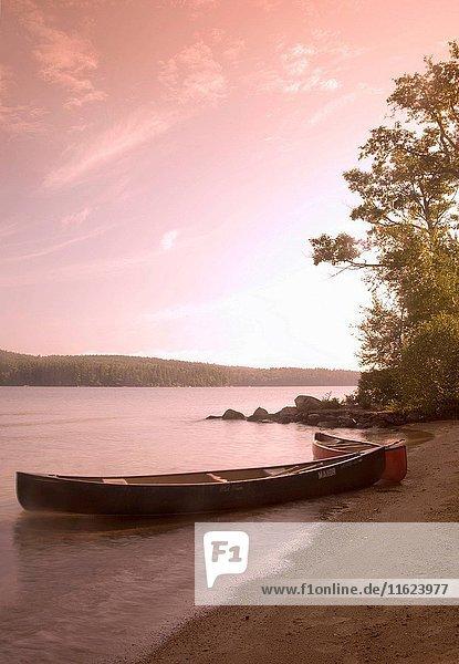 Kayak on shoreline at dusk with lake landscape behind  Squam Lake  Holderness  New Hampshire  USA.