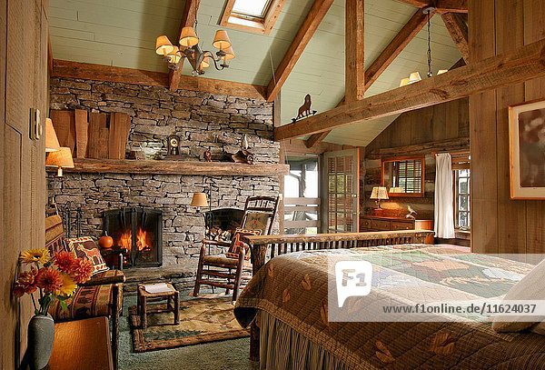 Wooden bed facing stone fireplace with lit fire in country style bedroom.