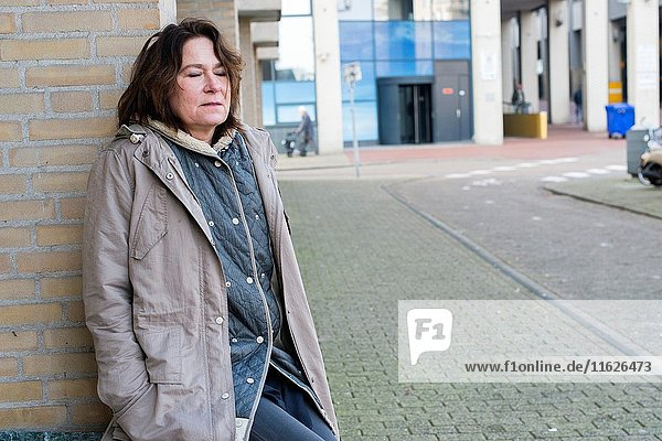 The Hague  Netherlands. Portrait of a mid adult woman hanging out and taking a break in the streets of town.
