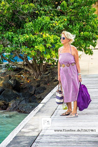 Caucasian retired senior woman looking at the wanter on the pier on her way to the local market in the tropical island of Martinique.
