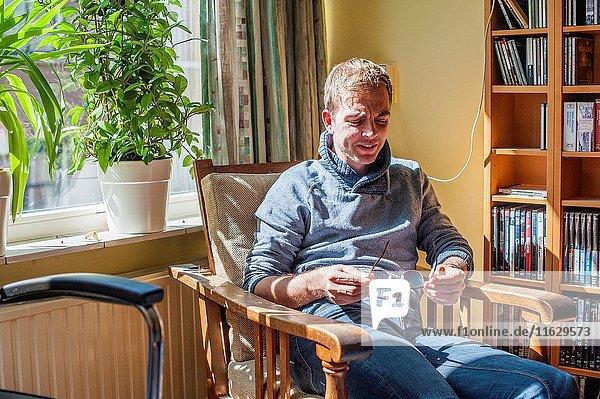 Tilburg  Netherlands. Living room portrait of an emotional young man.