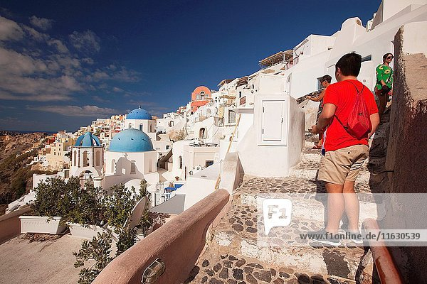 Tourists taking photos of the blue domed churches in Oia village  Santorini  Cyclades Islands  Greek Islands  Greece  Europe