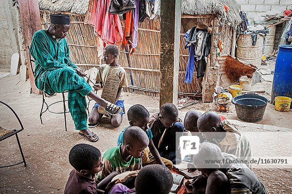 Marabout (Jamba Boubou) and talibe cleaning a tasbih. Also Talibes studying  in daara ( Koranic school)  Mbour  Senegal.