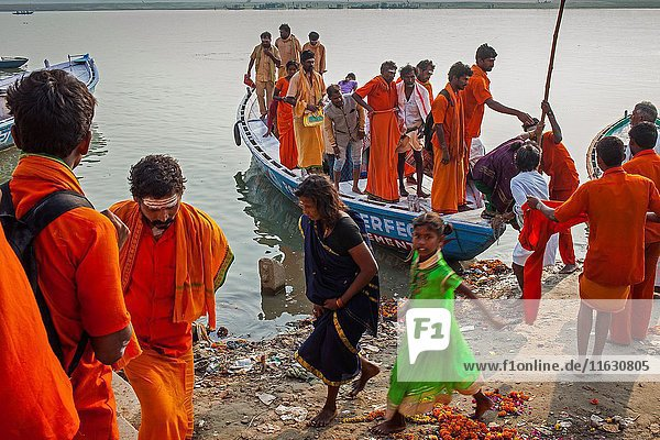 Pilgrims leaving a boat after sailing and praying in the river  in ghats of Ganges  river  Varanasi  Uttar Pradesh  India.