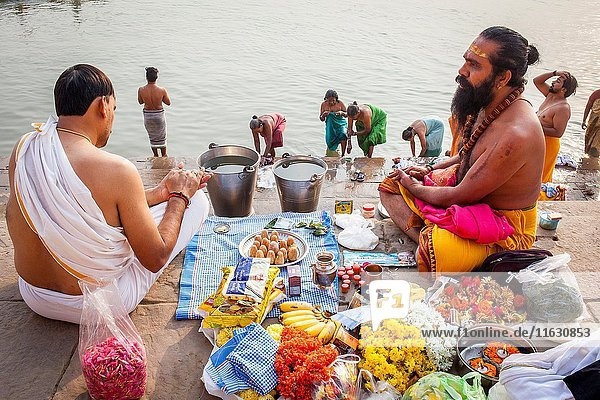 A Pandits (holy man and priest who performs ceremonies) preparing offerings and praying  on the ghats of Ganges river  in background pilgrims bathing  Varanasi  Uttar Pradesh  India.