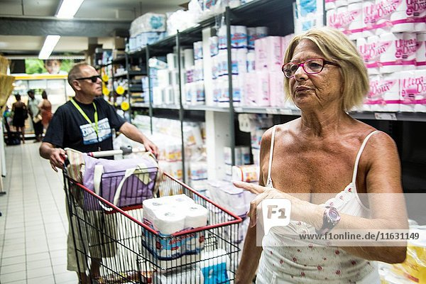 Mature retired senor caucasian woman doing her grocery shopping on vacation while her husband push the cart.